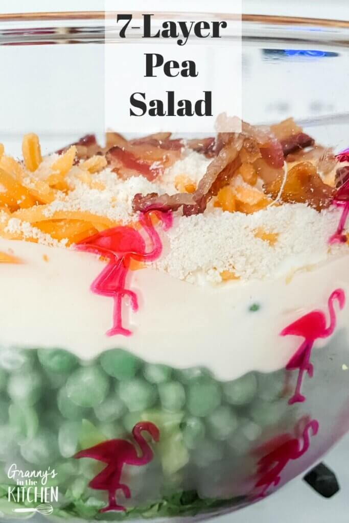close up of a layered pea salad in glass bowl