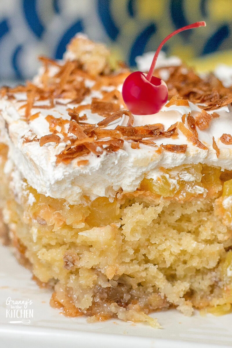 close up of piña colada cake with pineapple and whipped cream