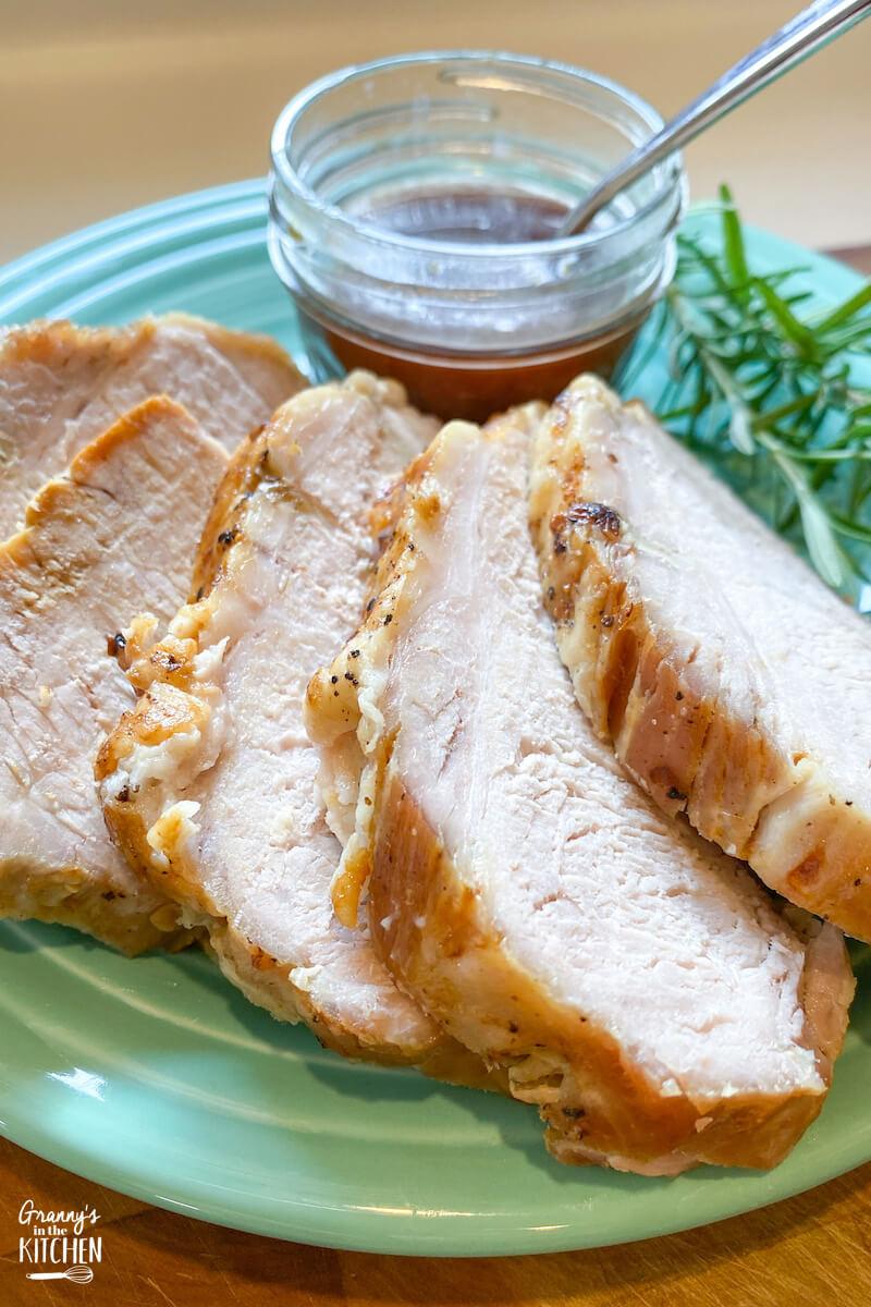 pork roast sliced on dinner plate with rosemary