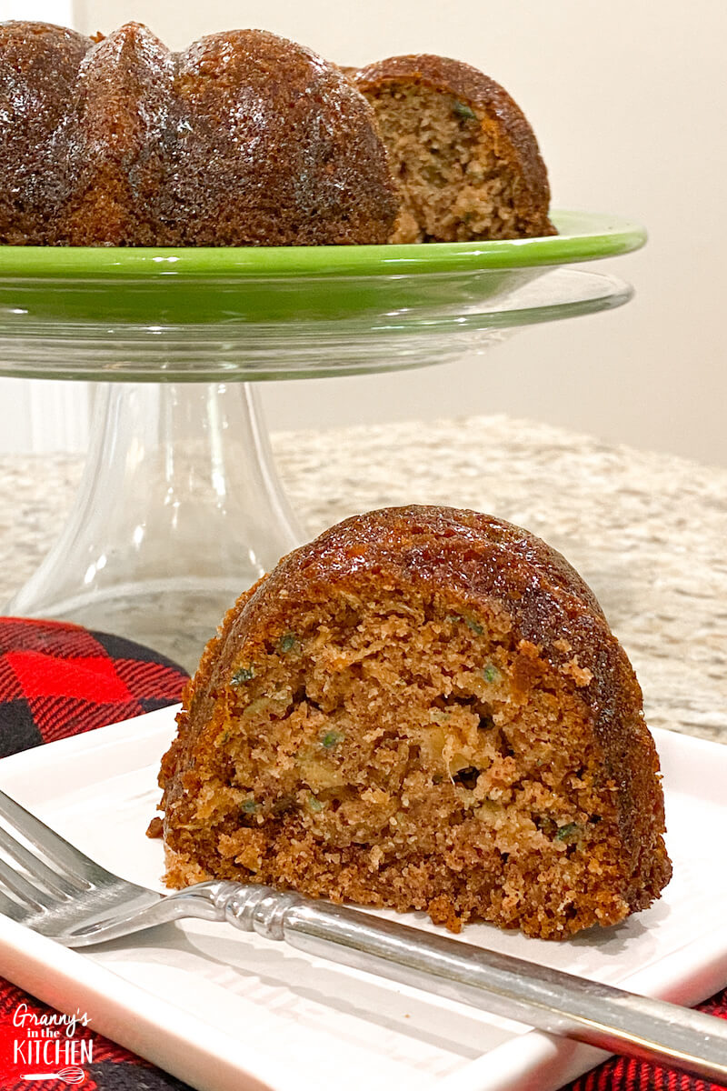 zucchini bread on plate with full cake in background