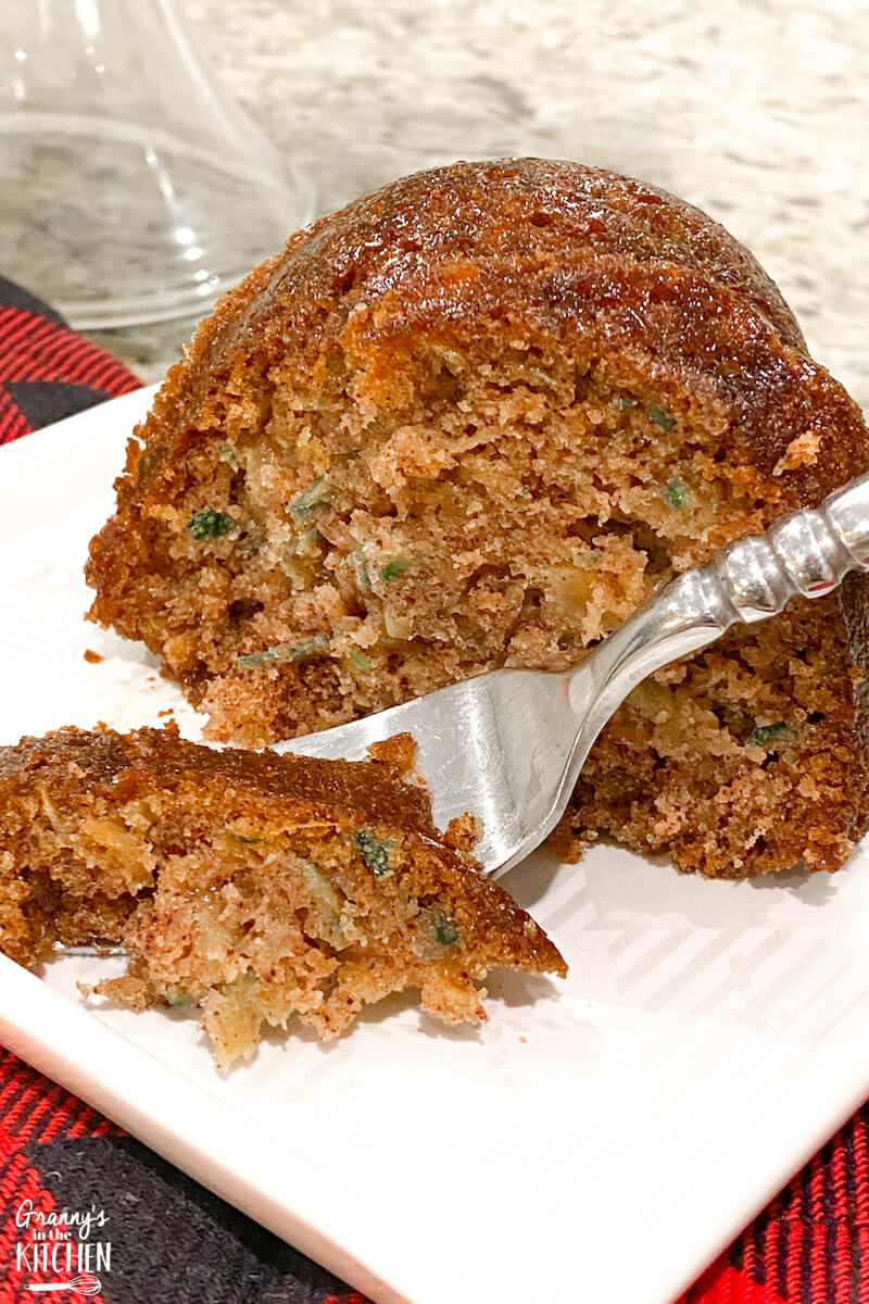 cutting a bite of zucchini cake with a fork