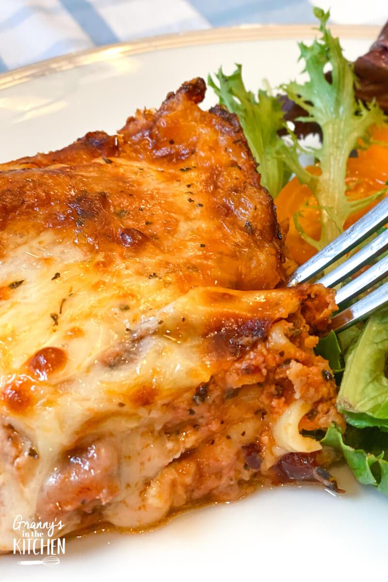 slice of homemade lasagna with salad