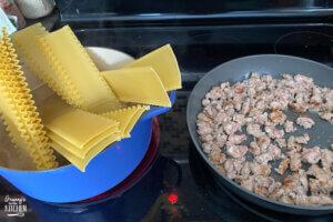 making lasagna noodles and sausage in pan