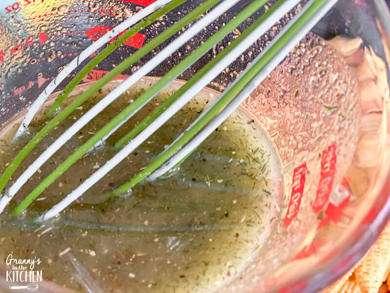 mixing ranch seasoning and oil with a whisk