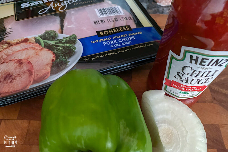 pork chops in package, veggies, and chili sauce on cutting board