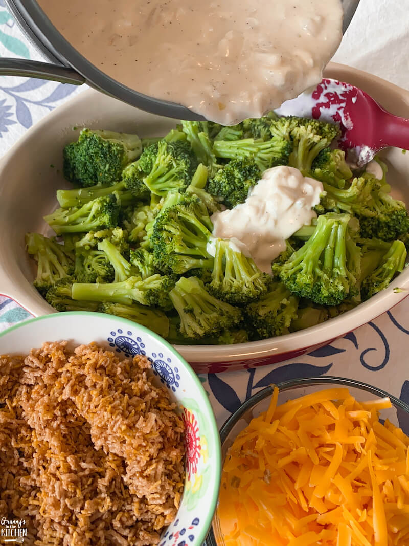 pouring cream sauce over steamed broccoli