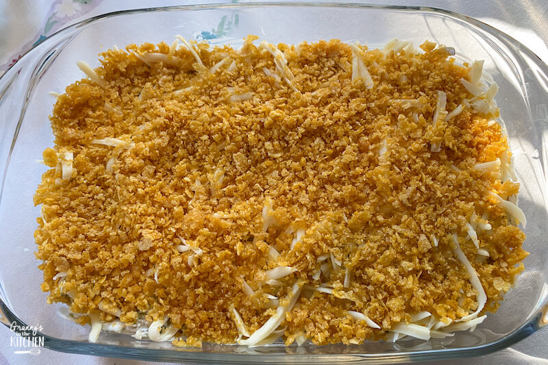 green bean casserole topped with corn flakes, ready to bake
