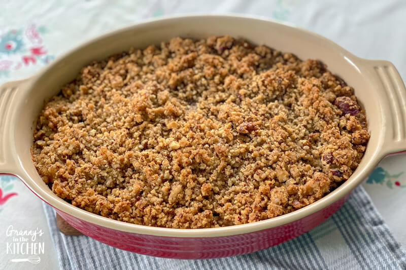 sweet potato casserole with pecan topping in red baking dish