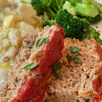 sliced meatloaf on plate with broccoli and potatoes