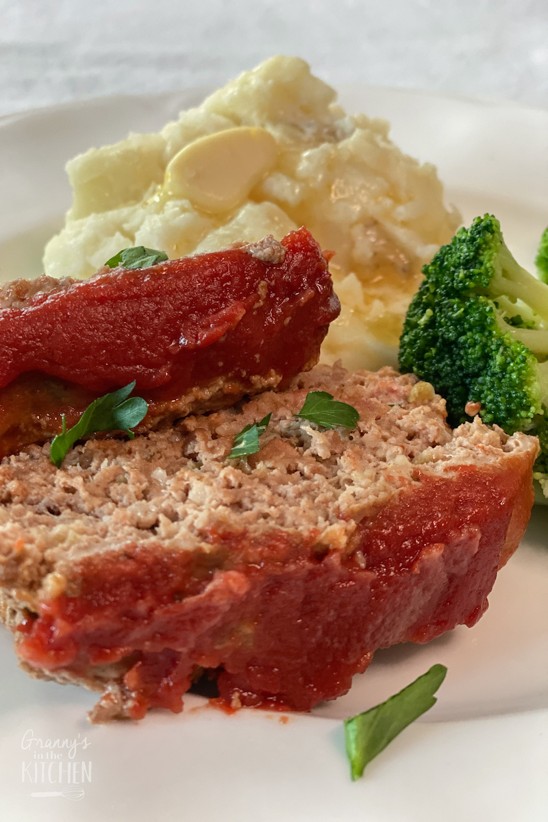 sliced meatloaf on plate with potato salad and broccoli