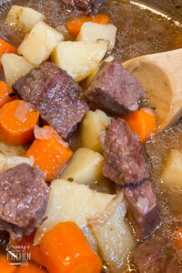 beef stew in pot with wooden spoon