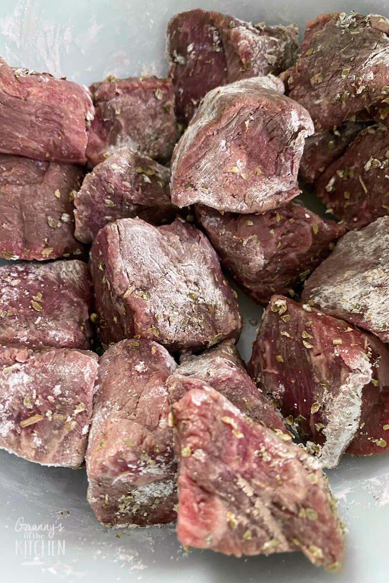 dredging beef cubes in cornstarch and spices