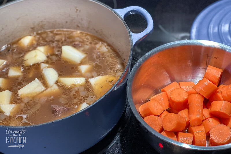 pot of beef stew and pot of carrots on stove