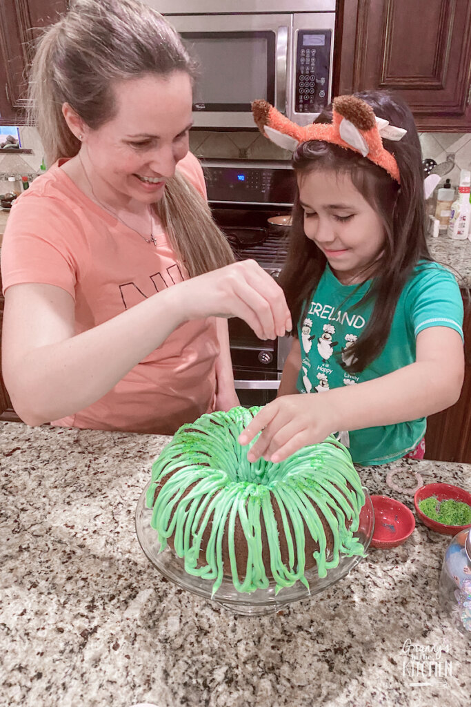 mom and daughter putting sprinkles on a green bundt cake