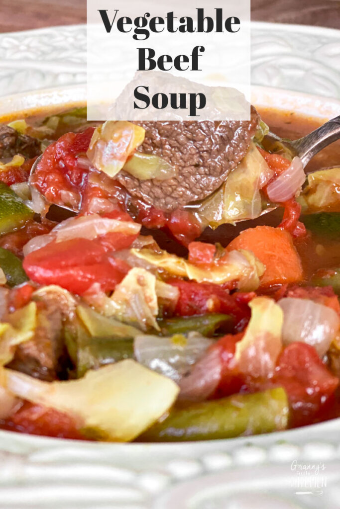 bowl of vegetable beef soup with beef cube on spoon