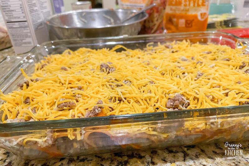 enchiladas topped with cheese ready to bake