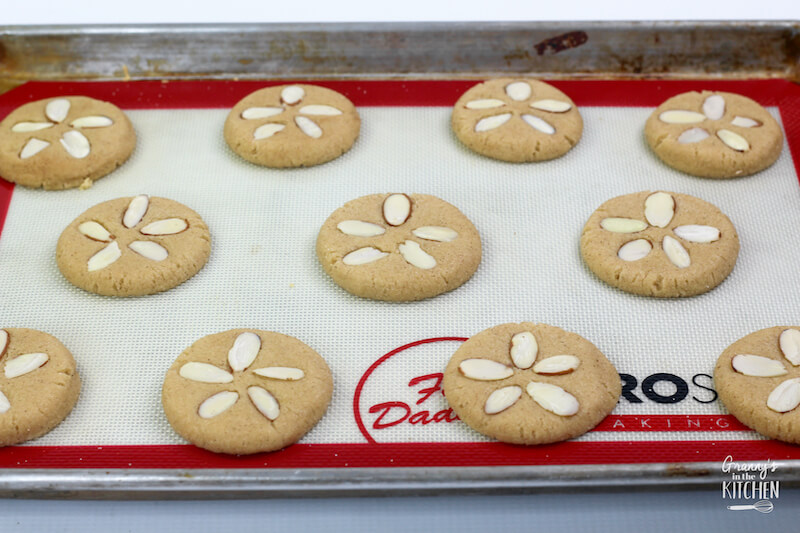 pressing almonds into cookies to look like sand dollars