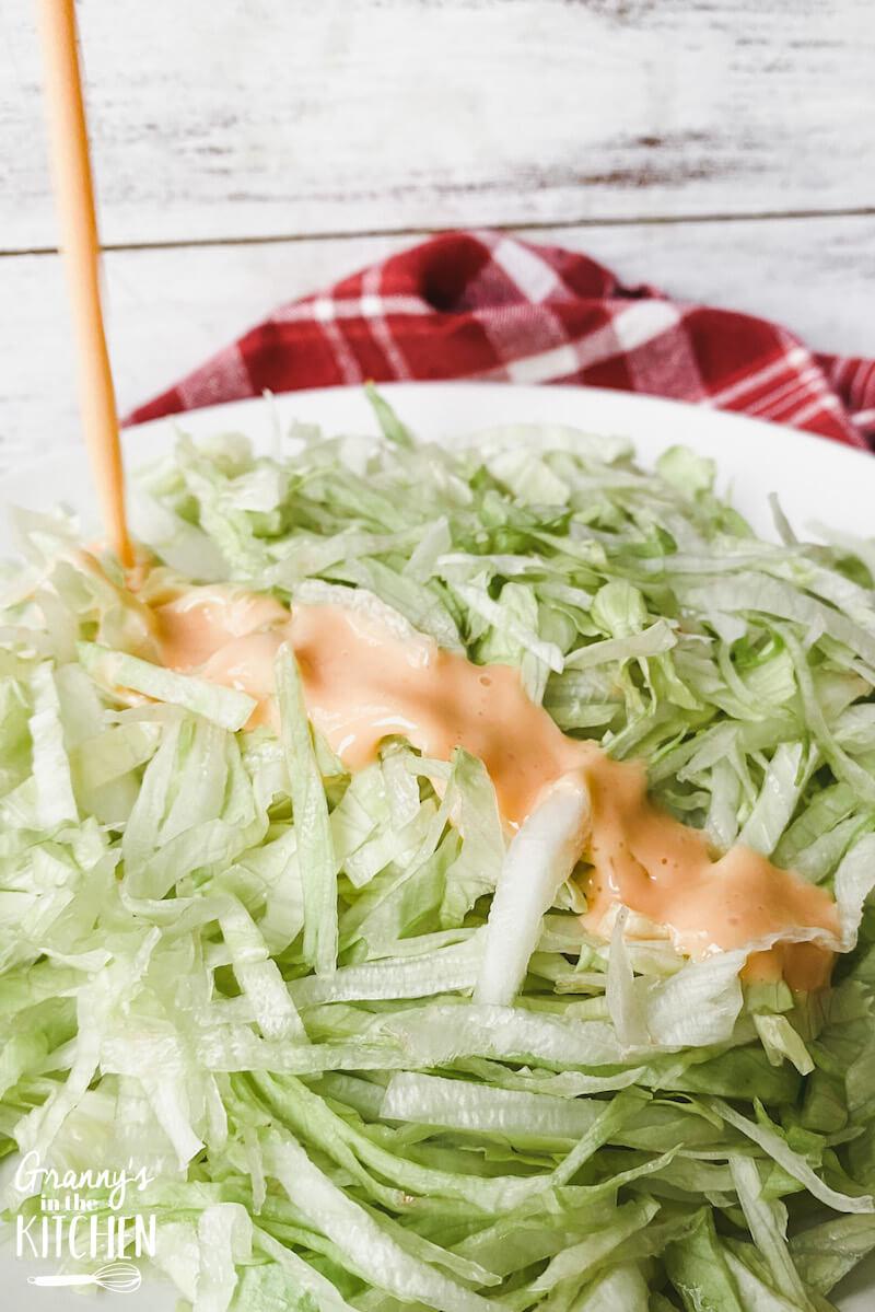 pouring French dressing on shredded lettuce